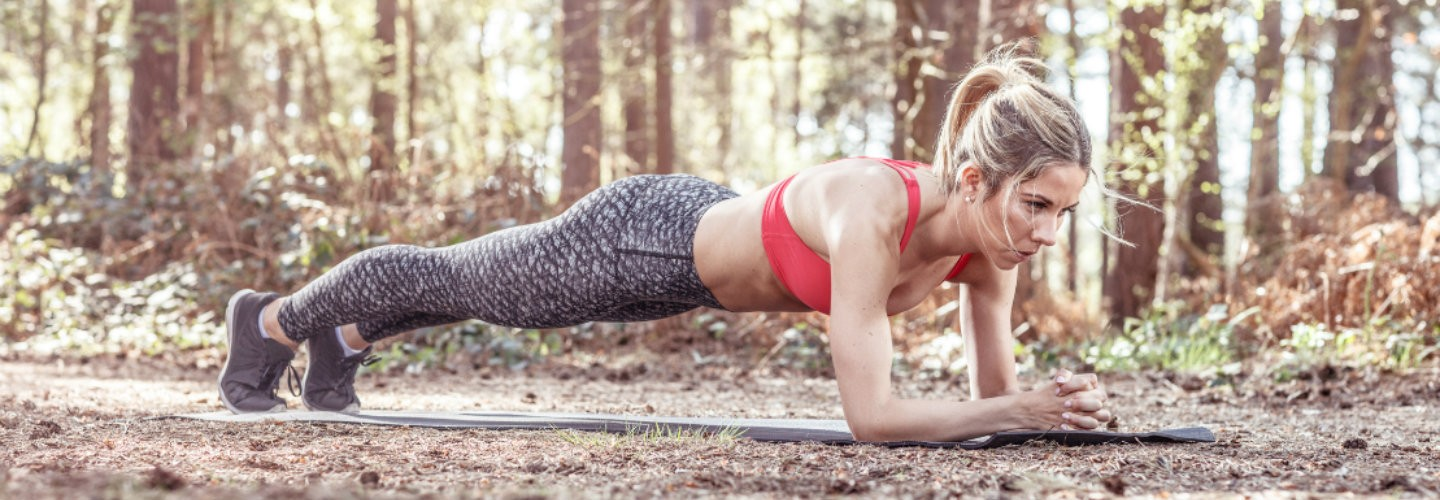 Woman performing plank exercise outdoors thumbnail