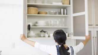 Woman Opening Kitchen Cabinets Cupboards thumbnail