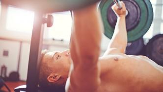 A man bench pressing in a gym