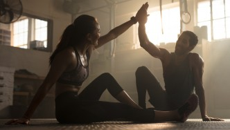 Fit-Couple-High-Fiving-In-Dark-Gym