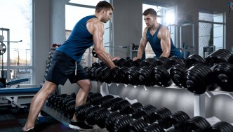 Male-At-Dumbbell-Rack-Looking-In-Mirror