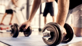 Man-Bent-Over-On-Mat-Grabbing-Adjustable-Dumbbell-Weights