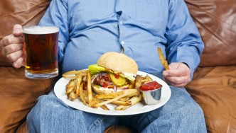 Hombre sentado con plato de comida y cerveza