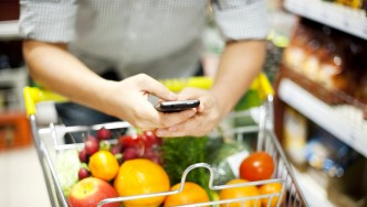 Man-On-Phone-Looking-At-Grocery-Shopping-List