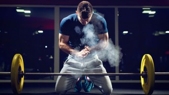 Man-Preparing-Barbell-Lift-Chalk-Cloud