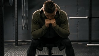 Man-Wearing-Hoodie-In-Gym-Stressed-Out-Worried