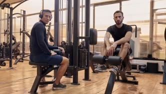 Two-Guys-Posing-In-Gym-Sitting-On-Machines