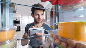 Young-Man-With-Note-Pad-Writing-Down-Food-List-Refrigerator