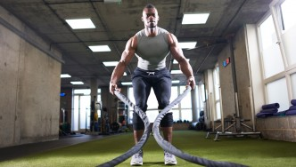 Man Working Out With Battle Ropes in Gym