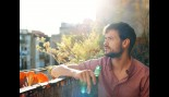 Man drinking beer on balcony thumbnail