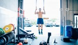 Man doing ring pullups in CrossFit-style gym thumbnail