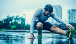 Man stretching legs on the ground in the rain thumbnail