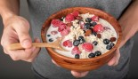Man holding bowl of healthy oatmeal with added fruit thumbnail