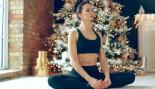 Miniatura de mujer meditando frente al árbol de navidad