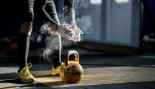 Man preparing to lift kettlebell at gym thumbnail