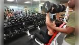 Woman Lifting Dumbbell Overhead At Gym thumbnail
