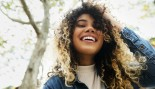 Smiling woman with hair in hand thumbnail
