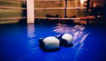 Blue Boxing Gloves Laying In The Ring  thumbnail
