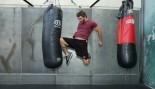 man throwing knee kick at heavy bag thumbnail