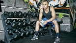 man resting in gym by dumbbell rack thumbnail