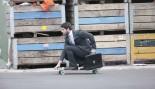 man skateboarding to work in suit thumbnail