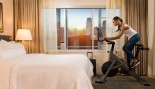 Woman riding stationary bike in hotel room thumbnail