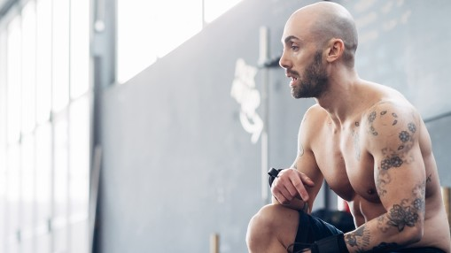 Portrait of tattooed man in gym looking away thumbnail