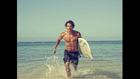 Man coming out of ocean with surf board thumbnail