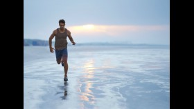 Man running along shore at beach thumbnail