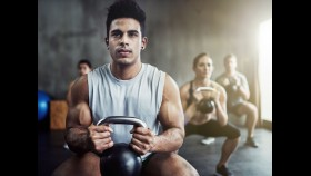 Workout class with men and women doing kettlebell goblet squats thumbnail