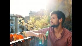 Man drinking beer on balcony thumbnail