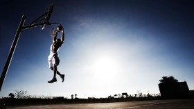 Man playing basketball, jumping and touching hoop thumbnail