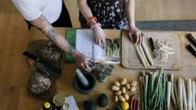 Couple cooking together with a cookbook thumbnail