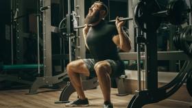 Miniatura del hombre barbudo luchando con la posición en cuclillas en la máquina Smith