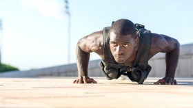 Black-Man-Doing-Pushups-Outdoors-With-A-Weighted-Vest miniatura