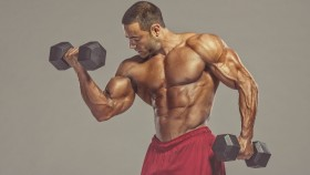 Bodybuilder curling dumbbell during arm workout thumbnail