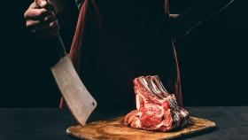 Butcher-Standing-Behind-Steak-Cuts-Cleaver. thumbnail