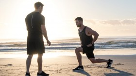Chris-Hemsworth-Training-With-Luke-Zocchi-Lunges-On-Beach-Sunrise miniatura