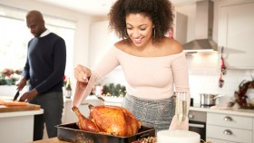 Couple-Preparing-Turkey-Dinner-Female-Basting-Turkey thumbnail