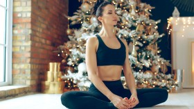 Female-Medititating-In-Front-Of-Christmas-Tree thumbnail