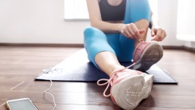 Fit-Female-In-Fitness-Clothes-Tying-Sneakers-At-Home thumbnail