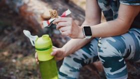 Fitness-Person-Sitting-On-Log-Holding-Eaten-Protein-Bar-And-Water-Bottle thumbnail