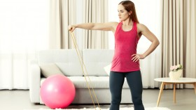 Fitness-Woman-Working-Out-At-Home-With-Bands-And-Swiss-Ball thumbnail