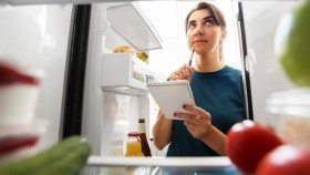 Girl-With-Notebook-Thinking-About-Food-In-Fridge thumbnail