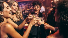 Group-Of-Friends-Celebrating-Drinking-At-Bar. thumbnail