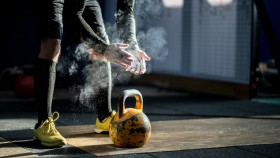 Man preparing to lift kettlebell at gym thumbnail