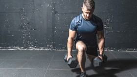 Man-Alone-Looking-Down-Doing-Dumbbell-Split-Squa thumbnail