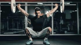 Man-Doing-Barbell-Squat-in-Dark-Gym thumbnail
