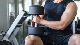 Man-Holding-Heavy-Dumbbell-On-Knee thumbnail