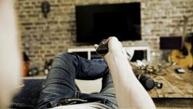 Man holding TV remote thumbnail